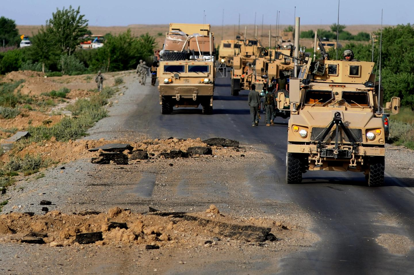 US Army vehicles make their way around blast holes caused by Improvised Explosive Devices, in Southern Afghanistan