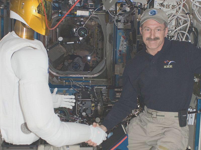 Astronaut Dan Burbank and NASA's Robonaut 2 shake hands in the ISS (Photo: NASA)