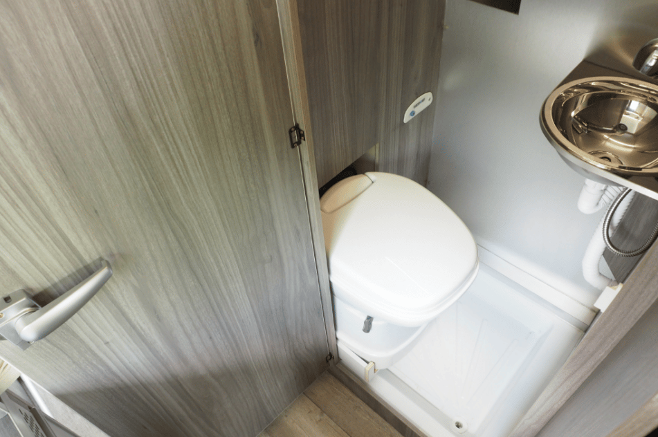 Just behind the rear two-seat bench, the slim bathroom includes a toilet and sink with shower faucet