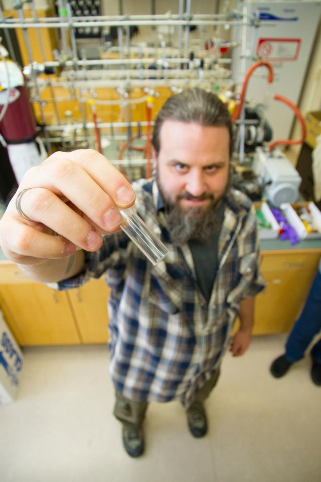 Stephen Foley holds a vial of the environmentally-friendly solution that his team has developed to extract gold from scrap electronics