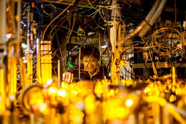 Graduate student Lawrence Cheuk adjusts the optics setup for laser cooling of sodium atoms.