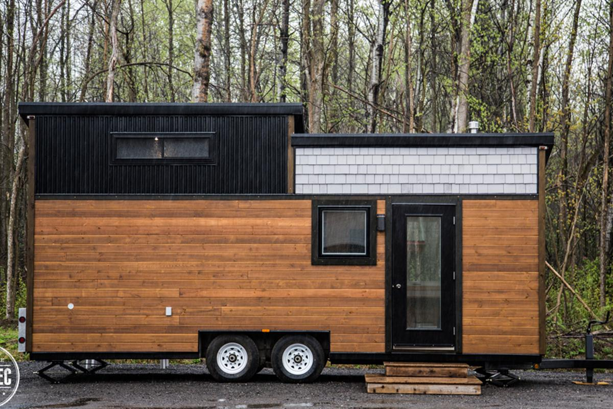 The tiny house is clad in white pine, stained western red cedar, and steel