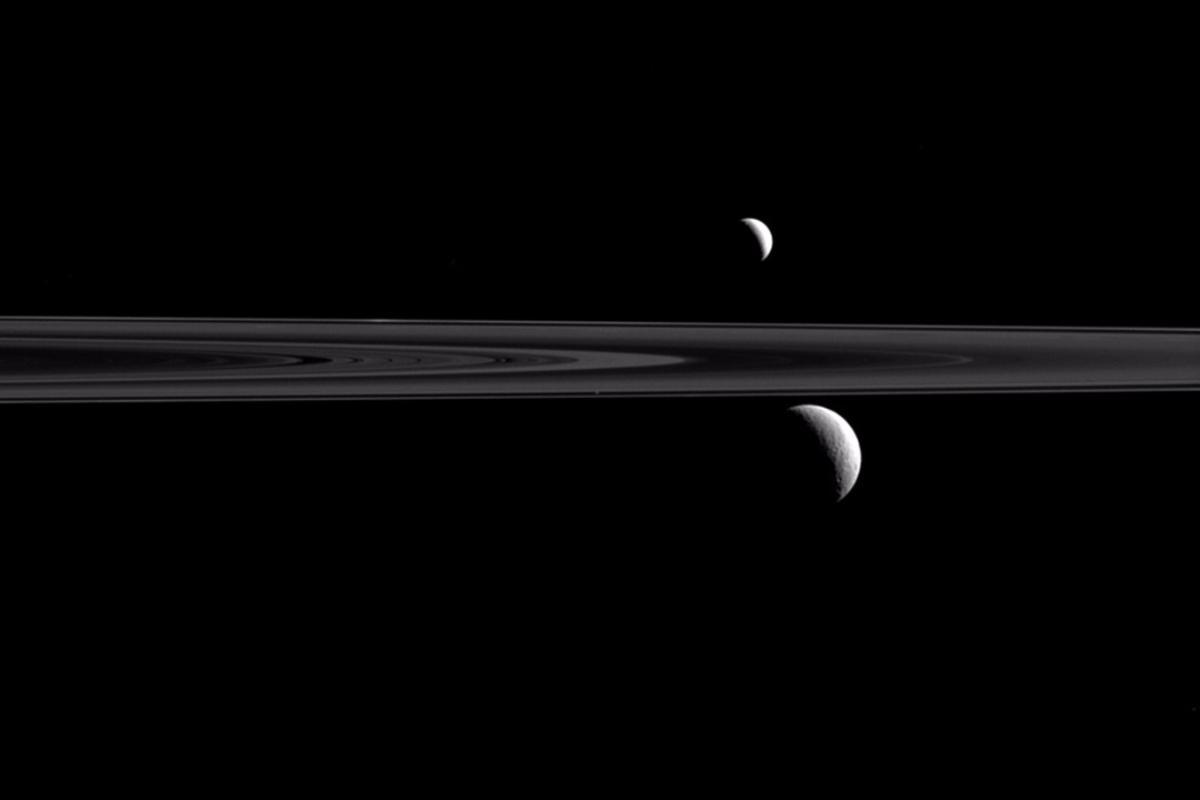 Saturn's rings divide Enceladus (top) and Rhea (below)
