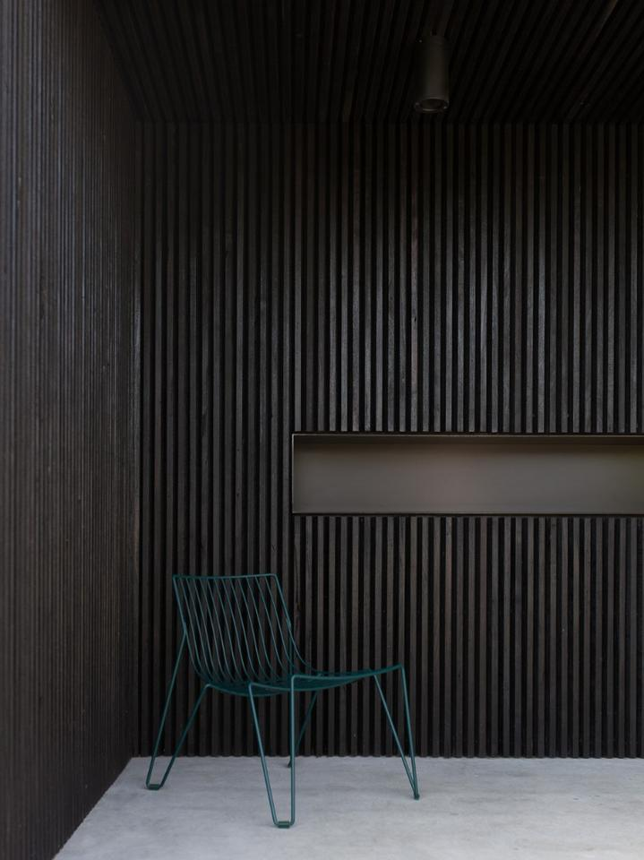 Black polished wooden slats clad sections of the home