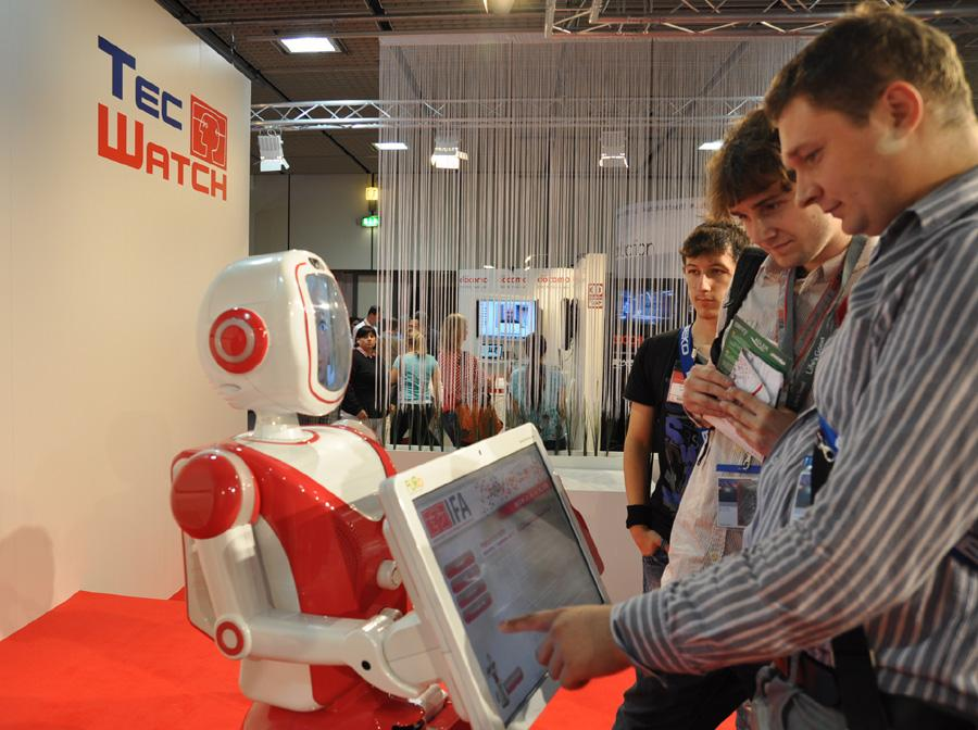 Visitors at IFA 2012 interact with Future Robot's service robot FURO.