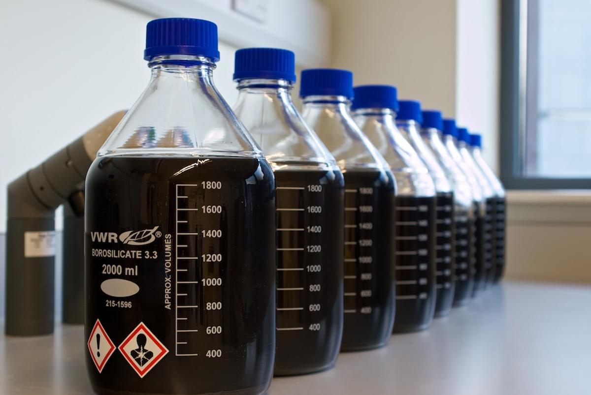 Bottles filled with water, detergent and graphene flakes – the graphene absorbs a small amount of light, leading to the darkened appearance of the mixture (Photo: CRANN)