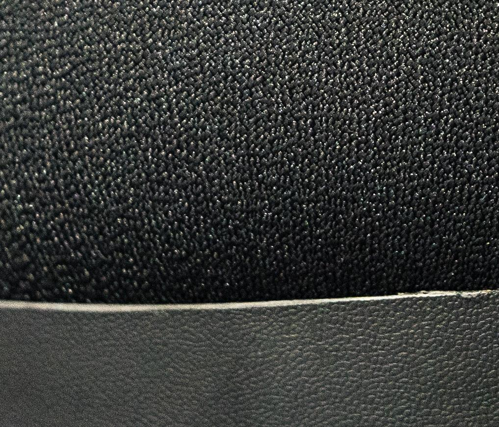 Close crop of the a9's view of a black chair in shadow under a table
