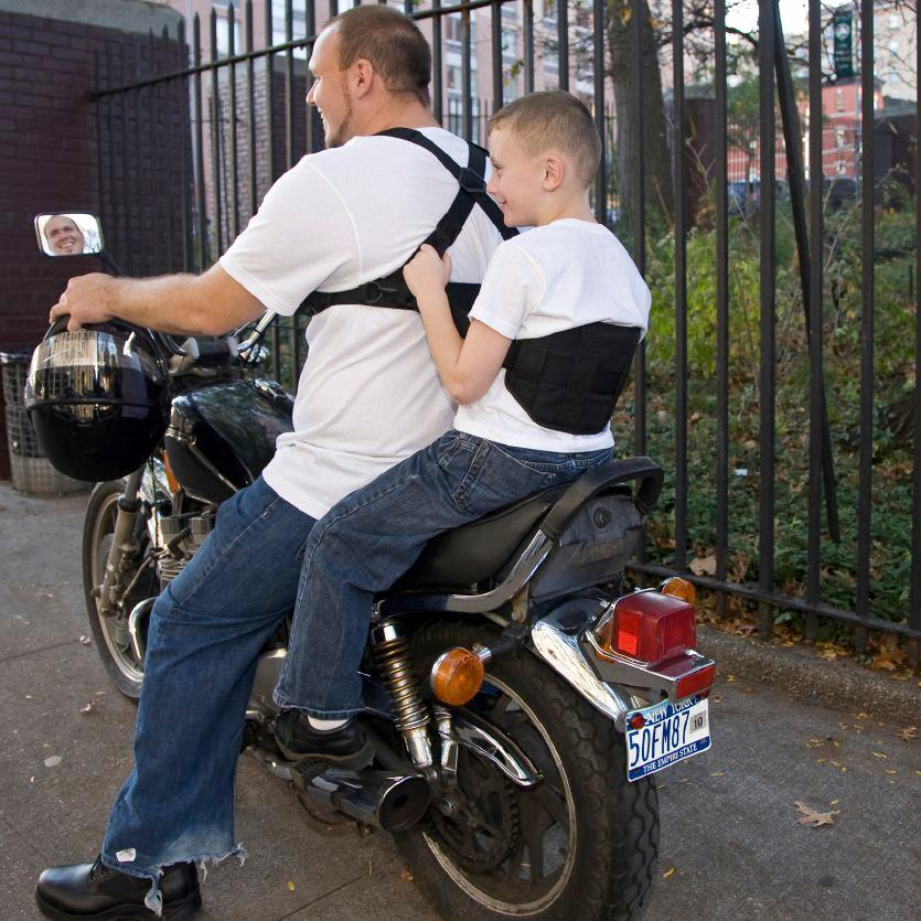 The Moto-Grip (seen here with the Moto-Grip Jr.) is a harness worn by a motorcycle operator, designed to let their passenger hang onto them better