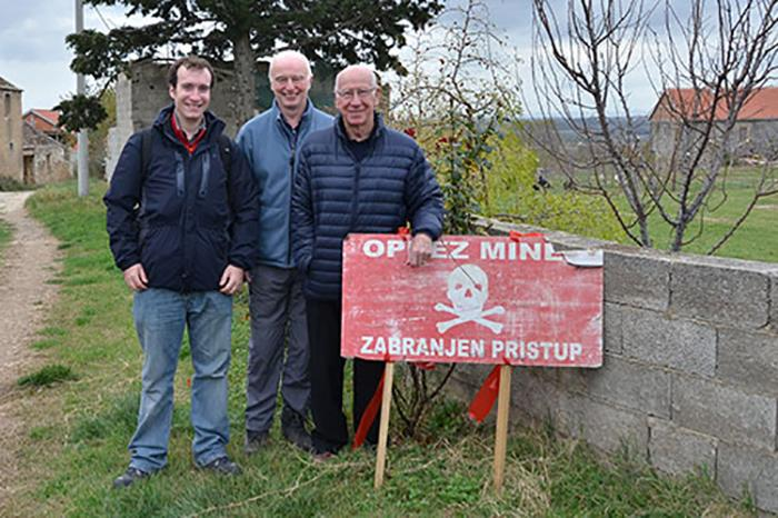 University of Bristol researchers Dr Oliver Payton and Dr John Day with Sir Bobby Charlton on a visit to mine clearance operations in Croatia
