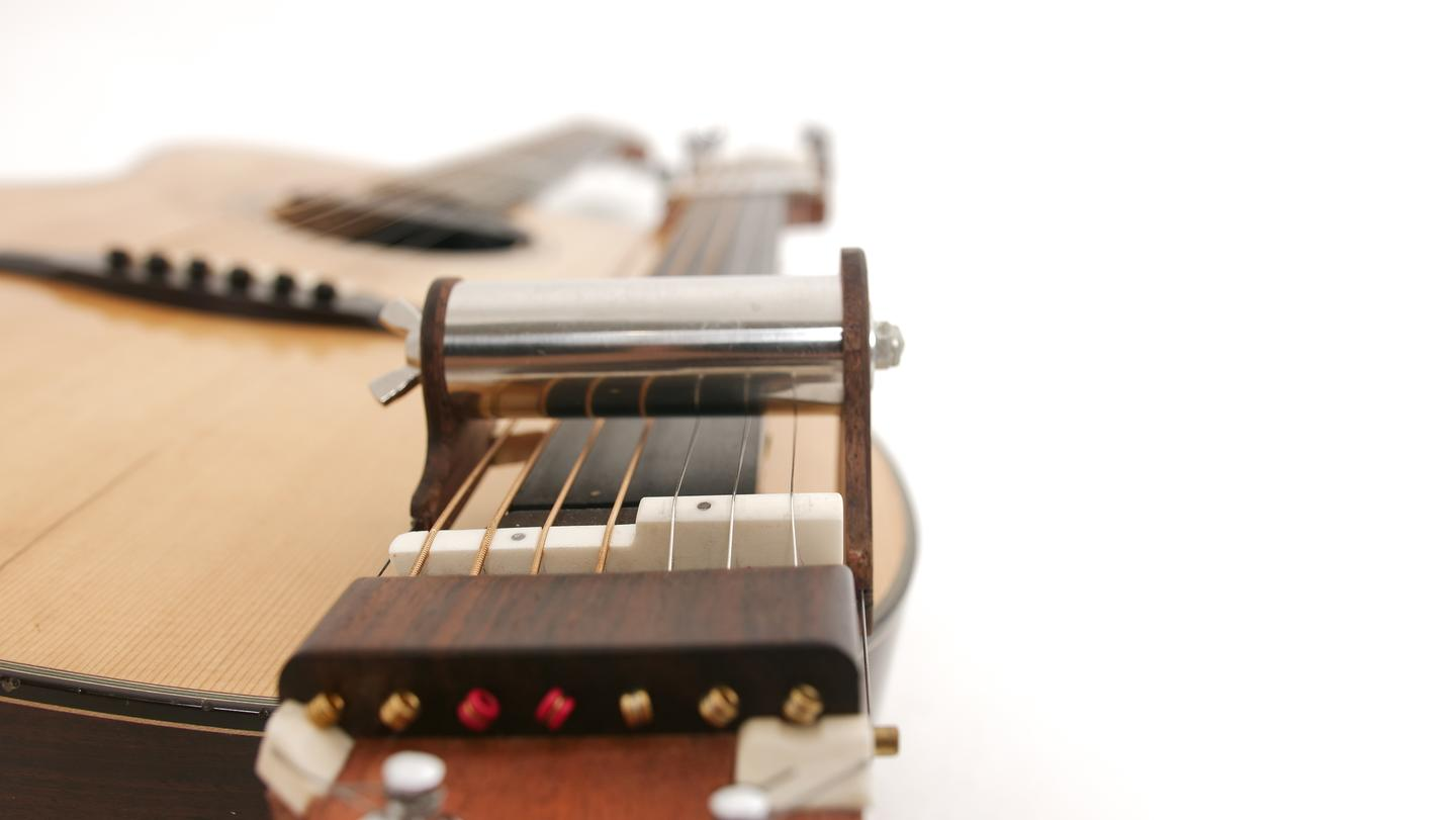 The four bass strings ride lower so that they are not influenced by the slide mechanism