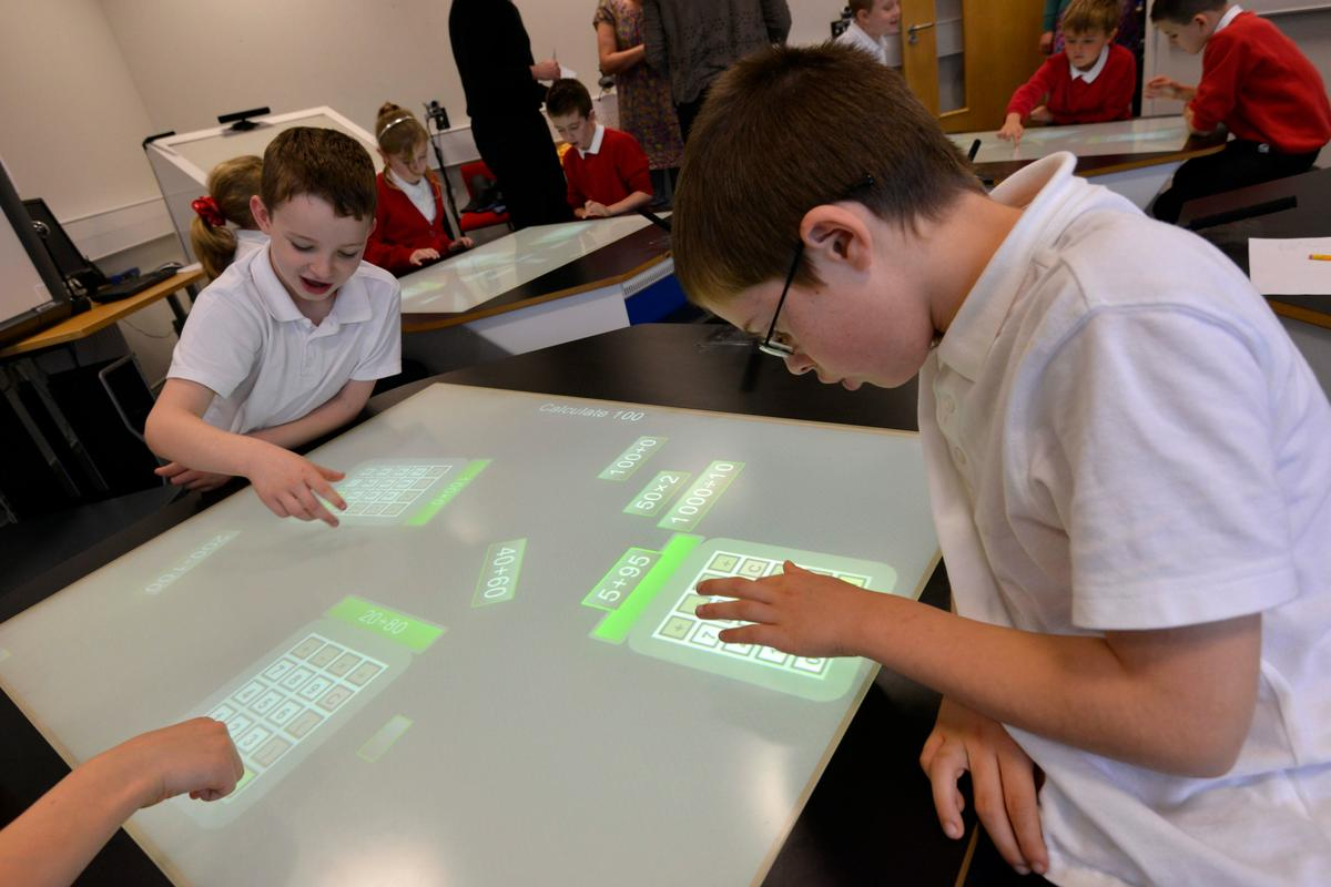 Students using the SynergyNet project's NumberNet desks