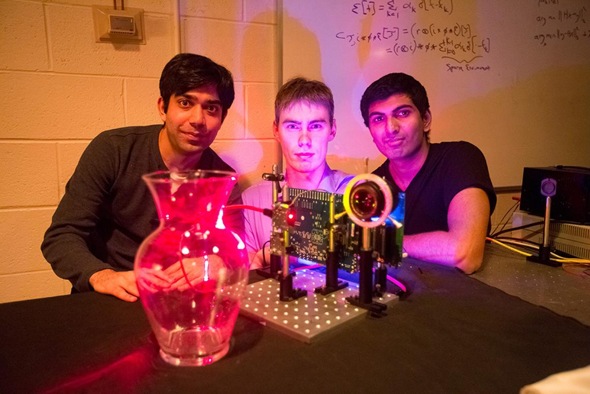 "MIT students (left to right) Ayush Bhandari, Refael Whyte and Achuta Kadambi pose next to their ""nano-camera"" that can capture translucent objects (Photo: Bryce Vickmark)"