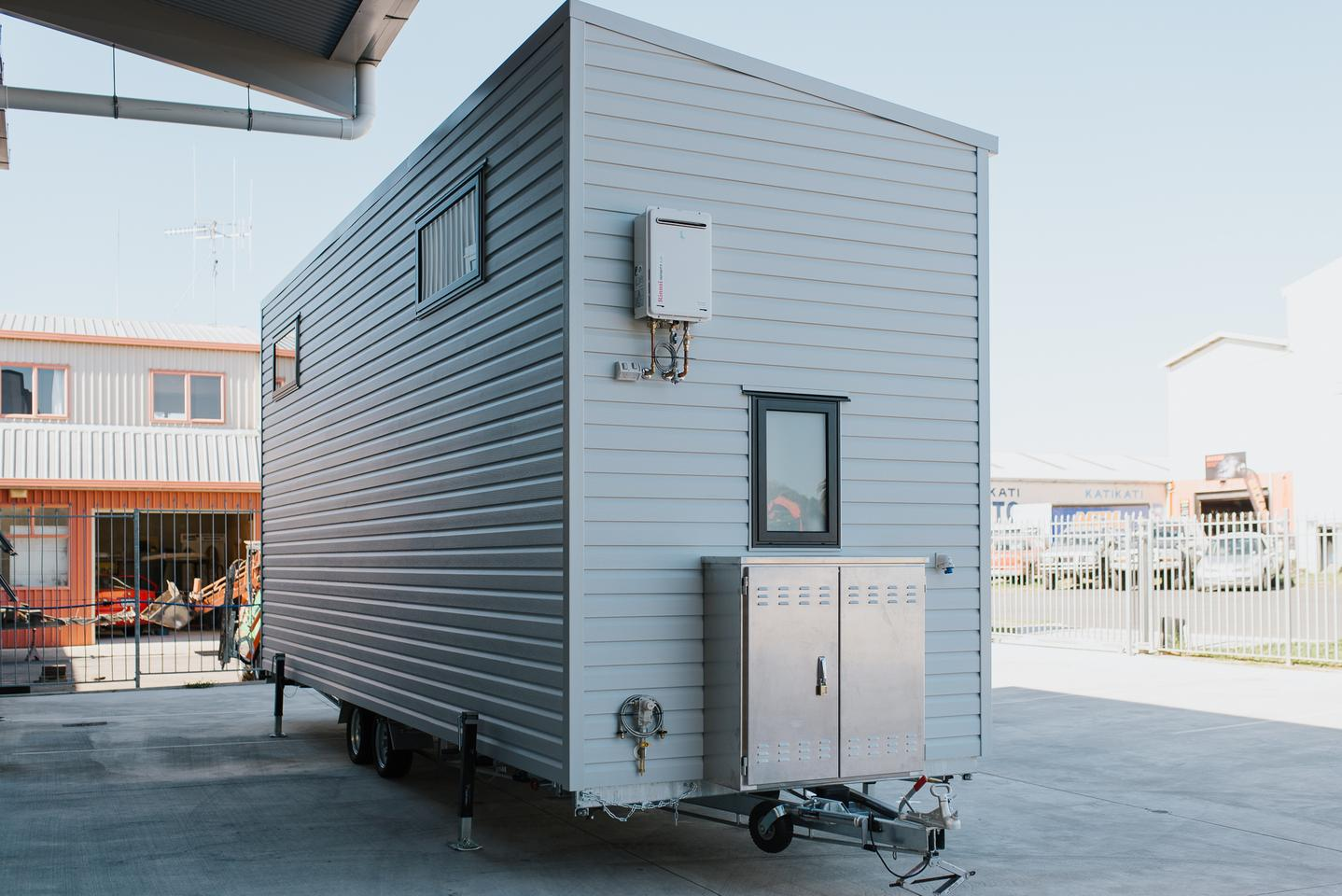 The Dreamweaver Tiny House has a storage box on its exterior that contains the inverter and batteries for the solar panel setup