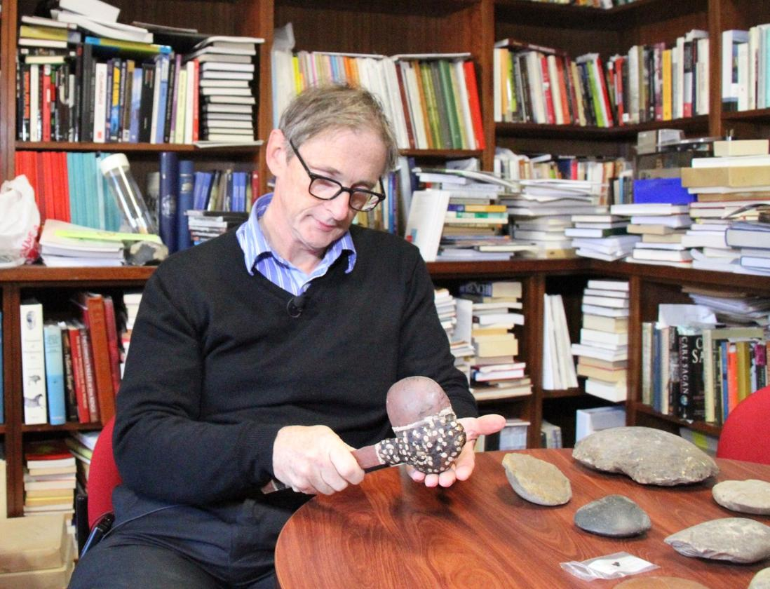 Professor Peter Hiscock, who led the study, holds a hafted axe – which he believes is indicative of the kind the fragment came from