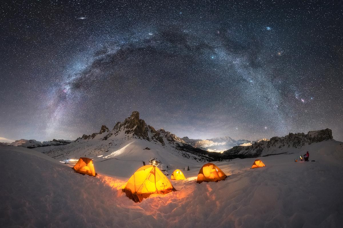 Base Camp, shot in the Dolomites, Italy. The warm glow of the tents contrasts the cool tones of the galaxy overhead.
