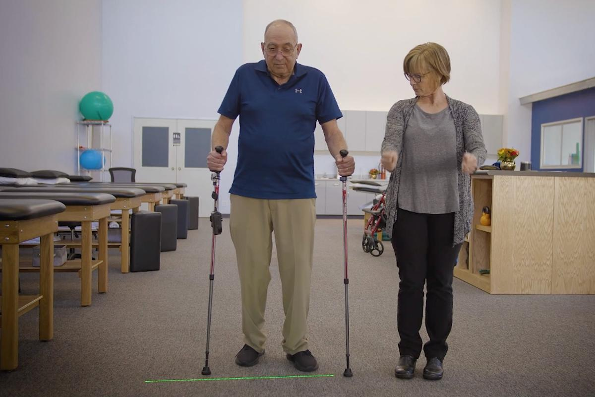 The NexStride system (mounted on left walking pole) provides users with a visual target to step over