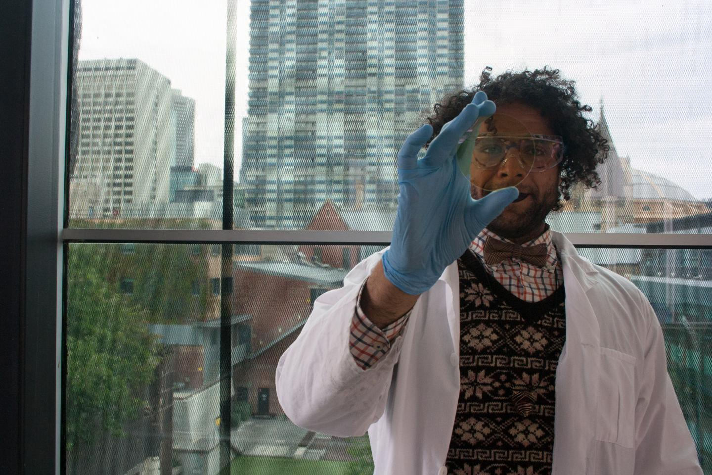PhD student Mohammad Taha with a sample of coated glass