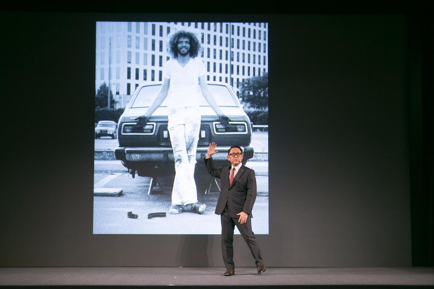 Akio Toyoda, President of Toyota Motor Corporation show a slide of a younger Gill Pratt in front of his Toyota Corolla