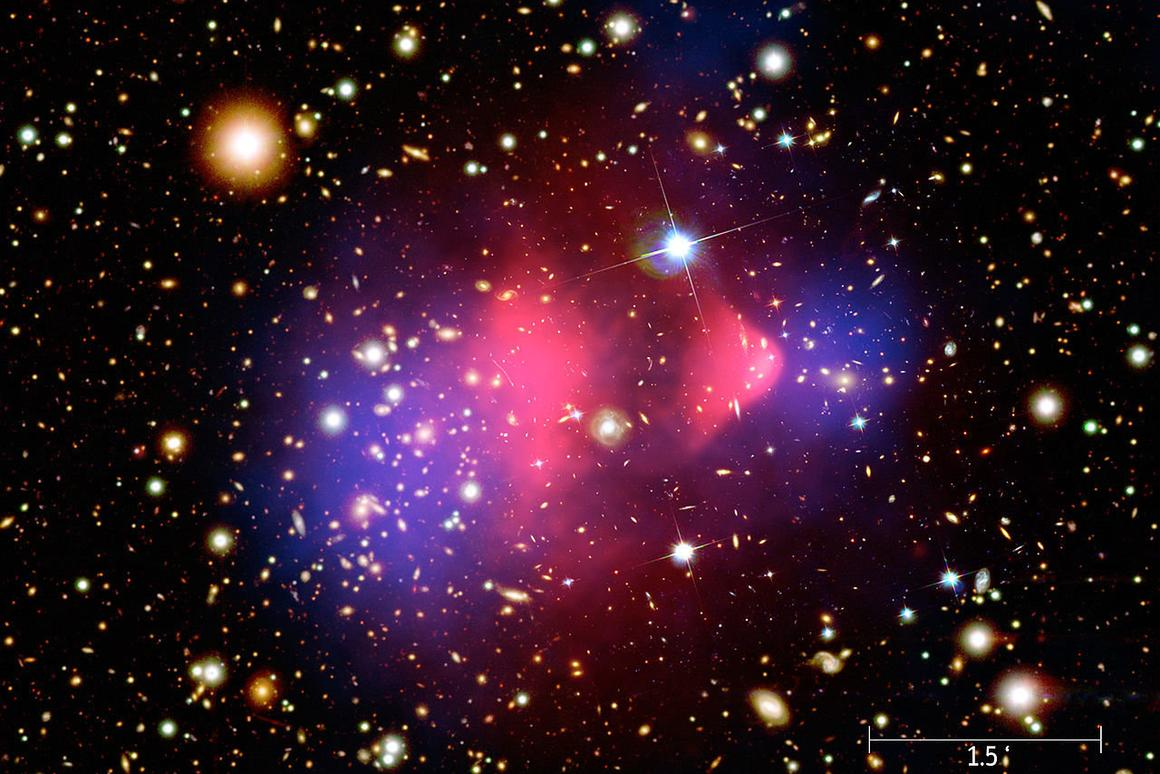 A composite image showing galaxies in optical light, x-ray emissions in pink and invisible mass – or dark matter – in blue.