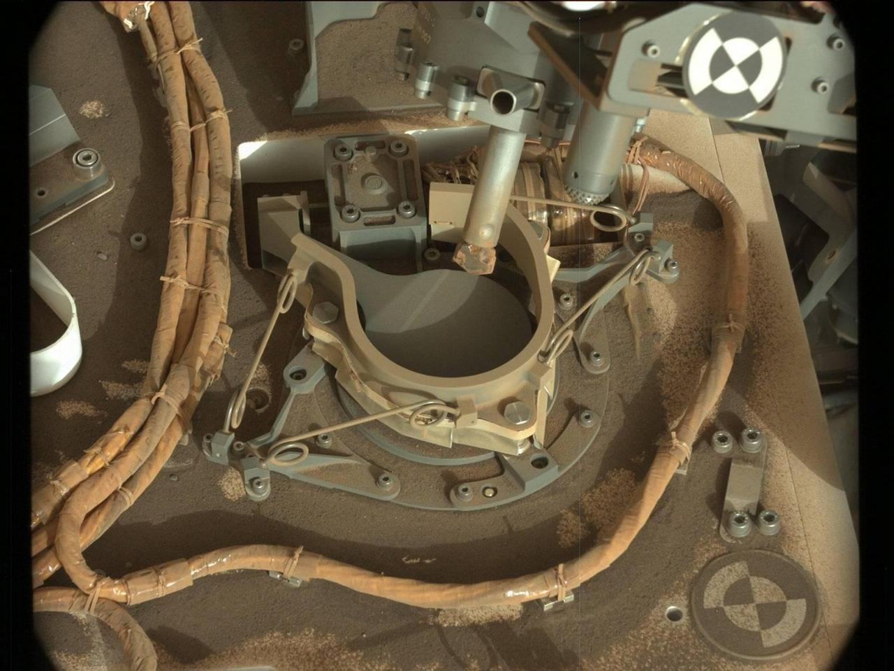 The drill bit of NASA's Curiosity Mars rover over one of the sample inlets on the rover's deck