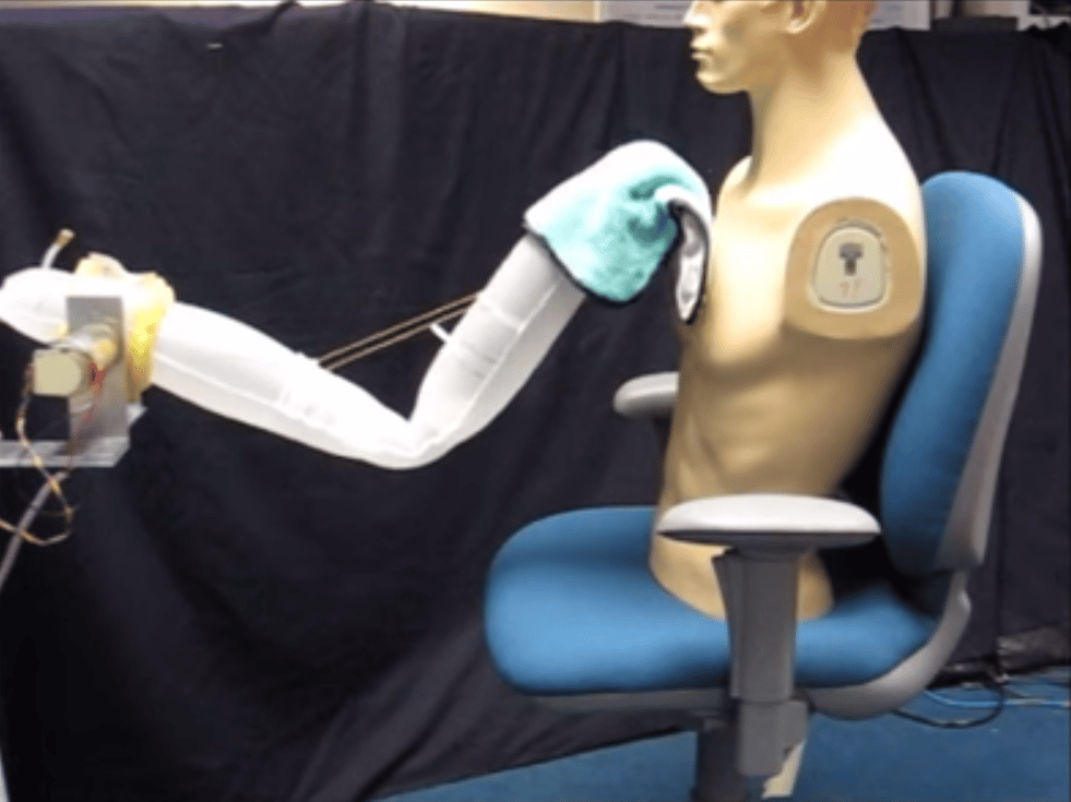 A soft robotic arm giving a mannequin a sponge bath