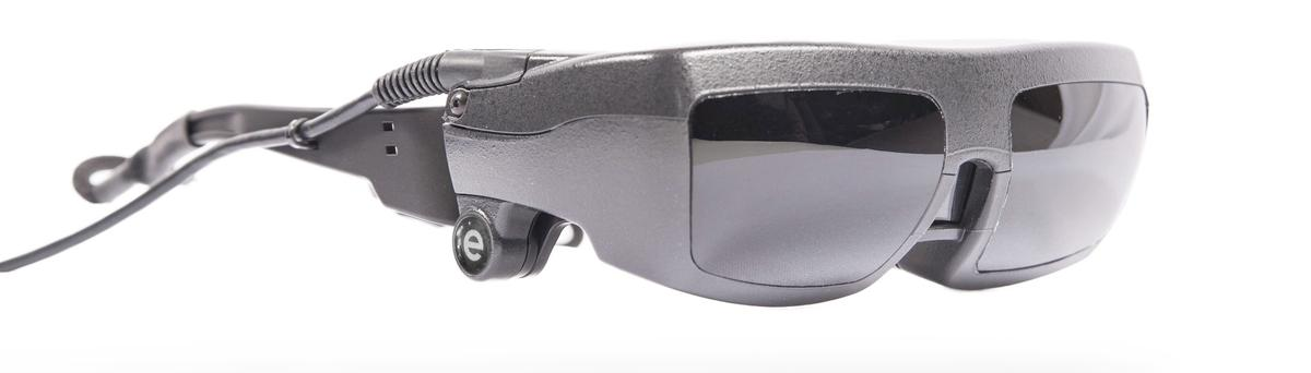 The eSight system consists of a frame that houses the user's prescription lenses, over top of which lies a headset containing an HD video camera and two LCD screens, along with a hand-held hard-wired control unit