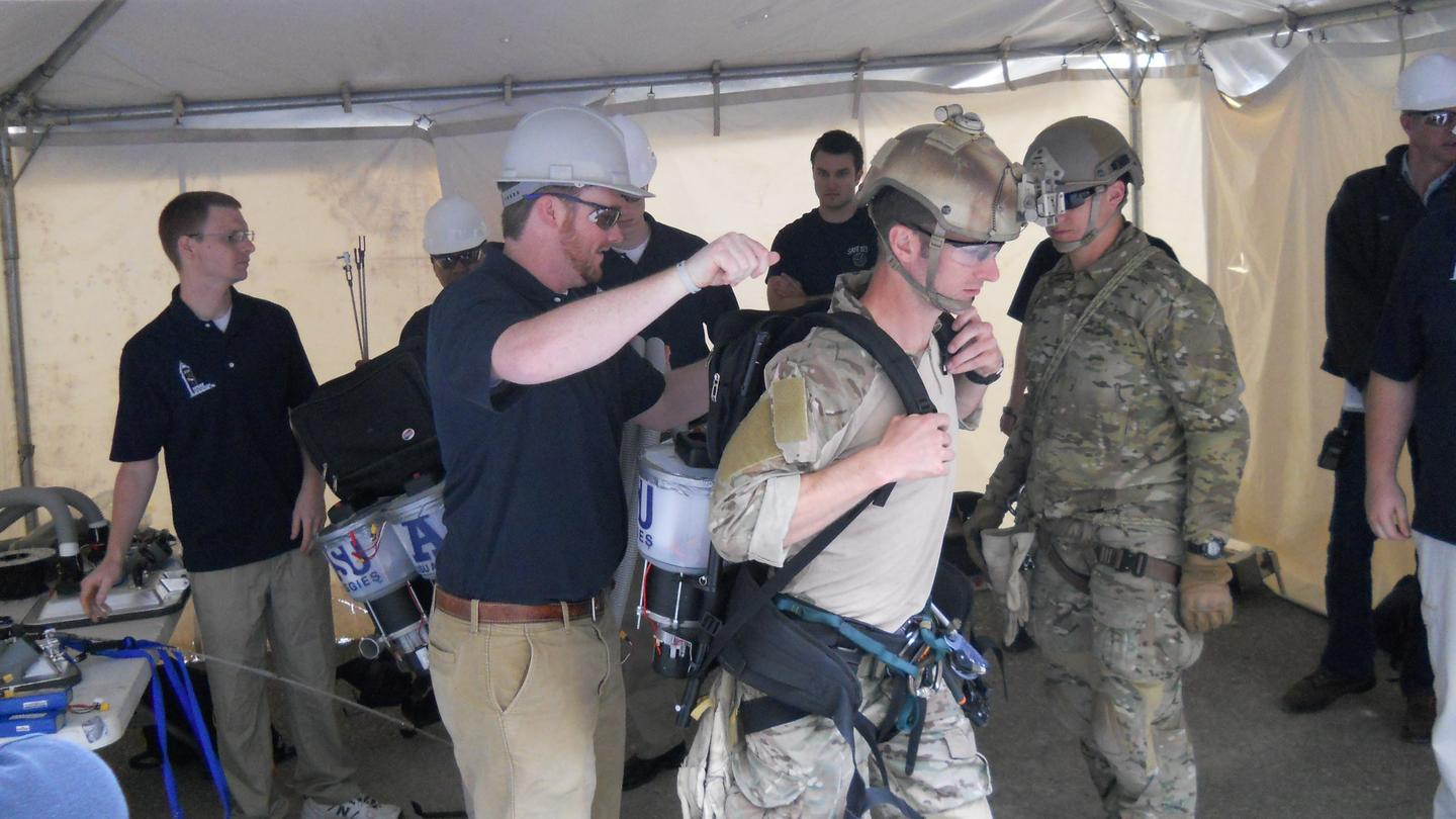 The Utah State University team, suiting up one of the Air Force-supplied climbers (Photo: USU)