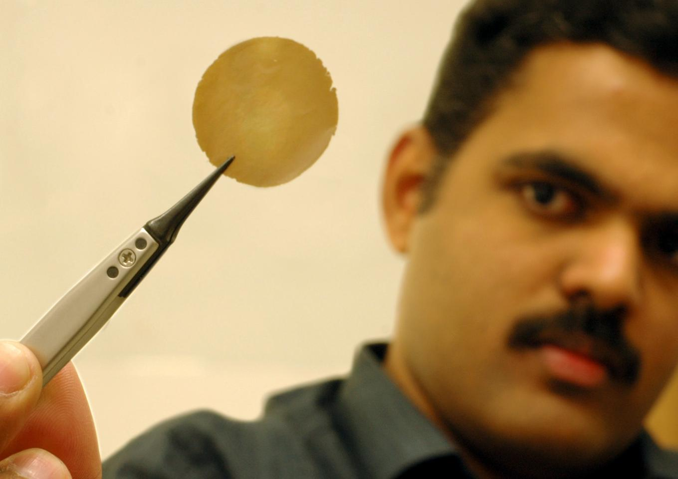 Dr Nair shows his one micron thick graphene oxide film research sample (Photo: University of Manchester)