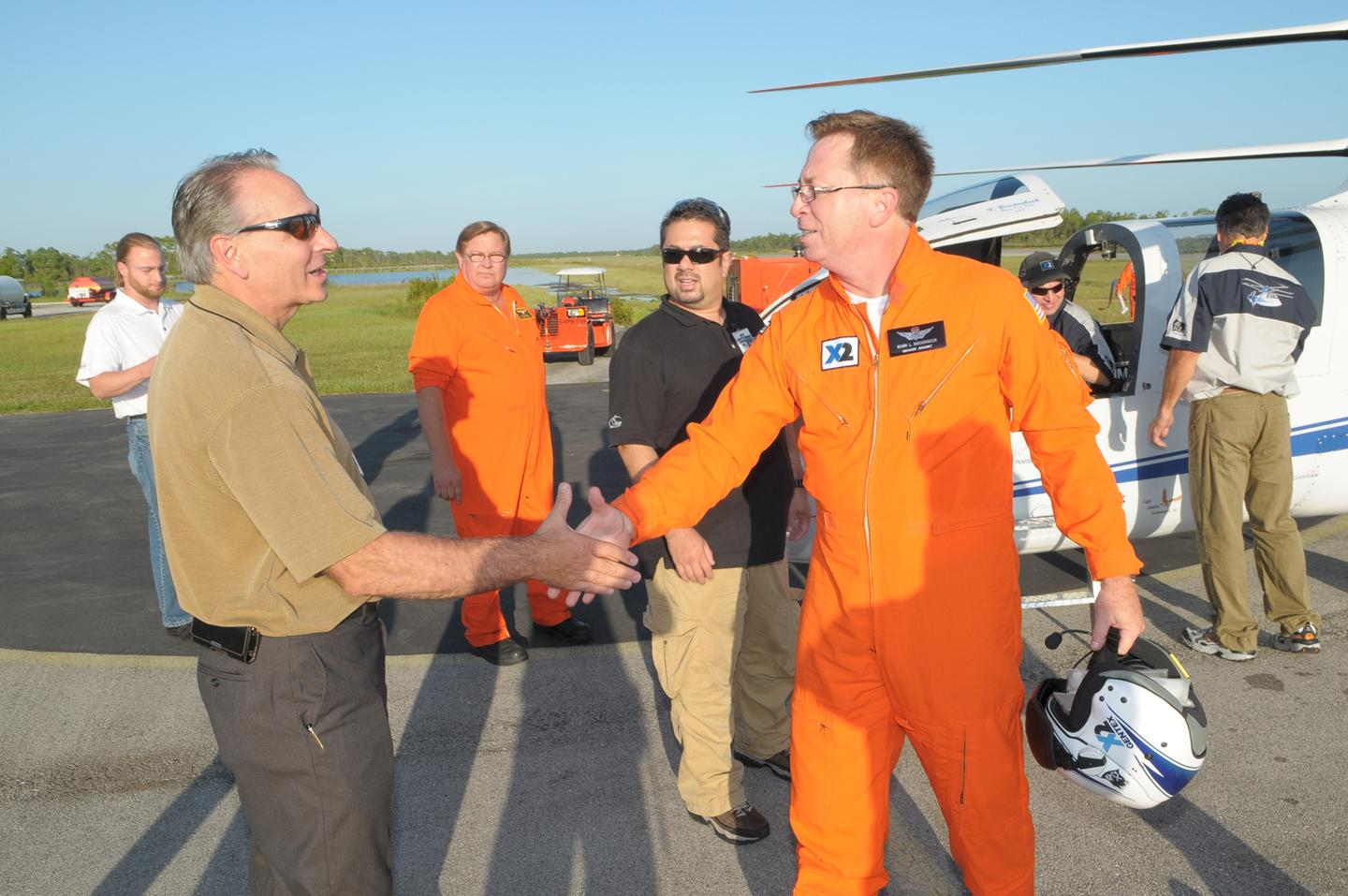 Sikorsky President Jeffrey Pino (left) shakes hands with Chief Pilot Kevin Bredenbeck after the flight