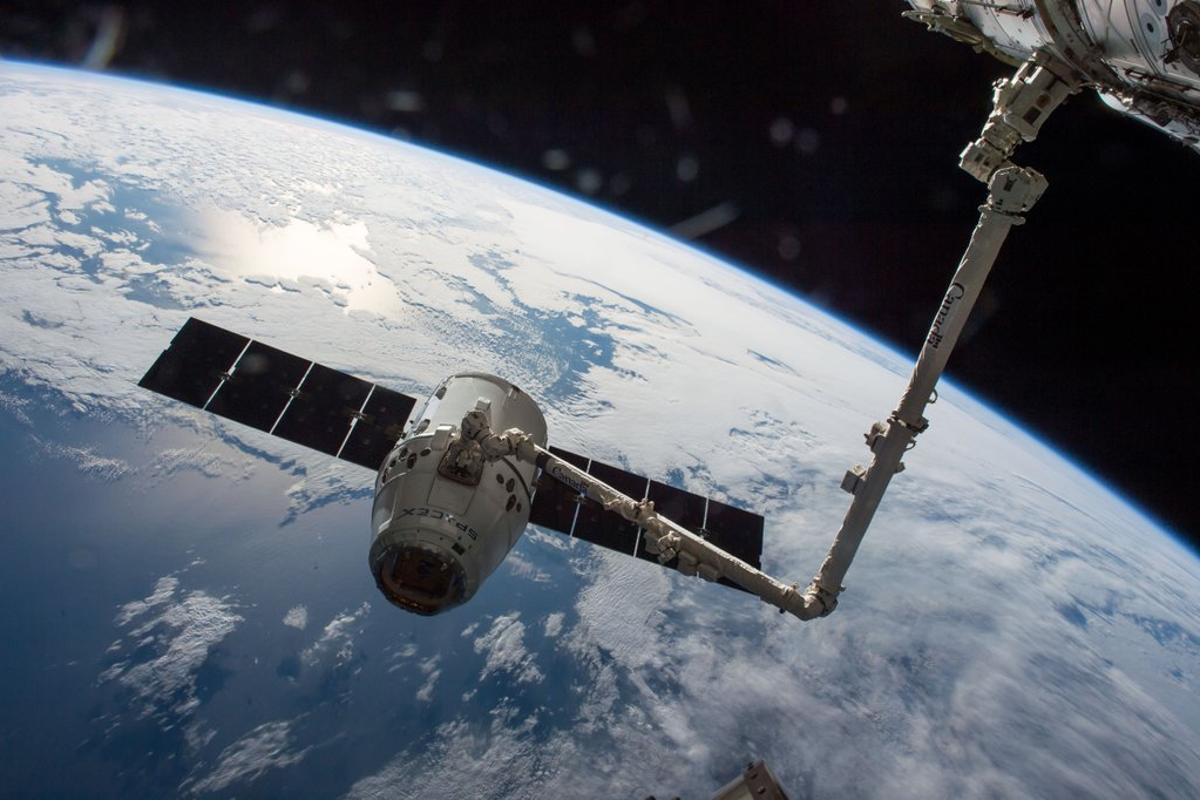 A robotic arm prepares Dragon for departure from the ISS