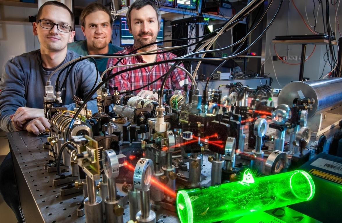 Michał Dąbrowski, Radek Chrapkiewicz and Wojciech Wasilewski at FUW have created an atomic memory (glowing green) for use with quantum technologies (Photo: FUW, R. Chrapkiewicz)