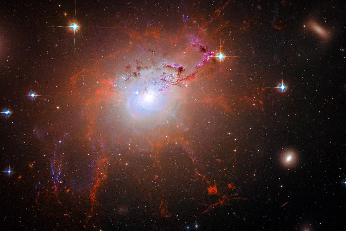 Image of NGC 1275 displaying filimentary structures of gas surrounding the galaxy in the centre (Image: NASA, MIT, Jose-Luis Olivares)