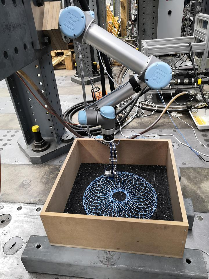 A robotic arm lays out a preprogrammed string pattern to reinforce the asphalt as part of road material research at Empa