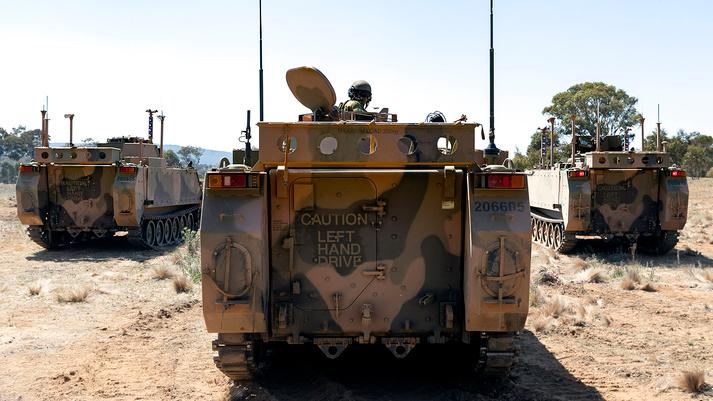 An Australian Army M113AS4 Crew Commander positions his vehicle behind two autonomous M113 AS4