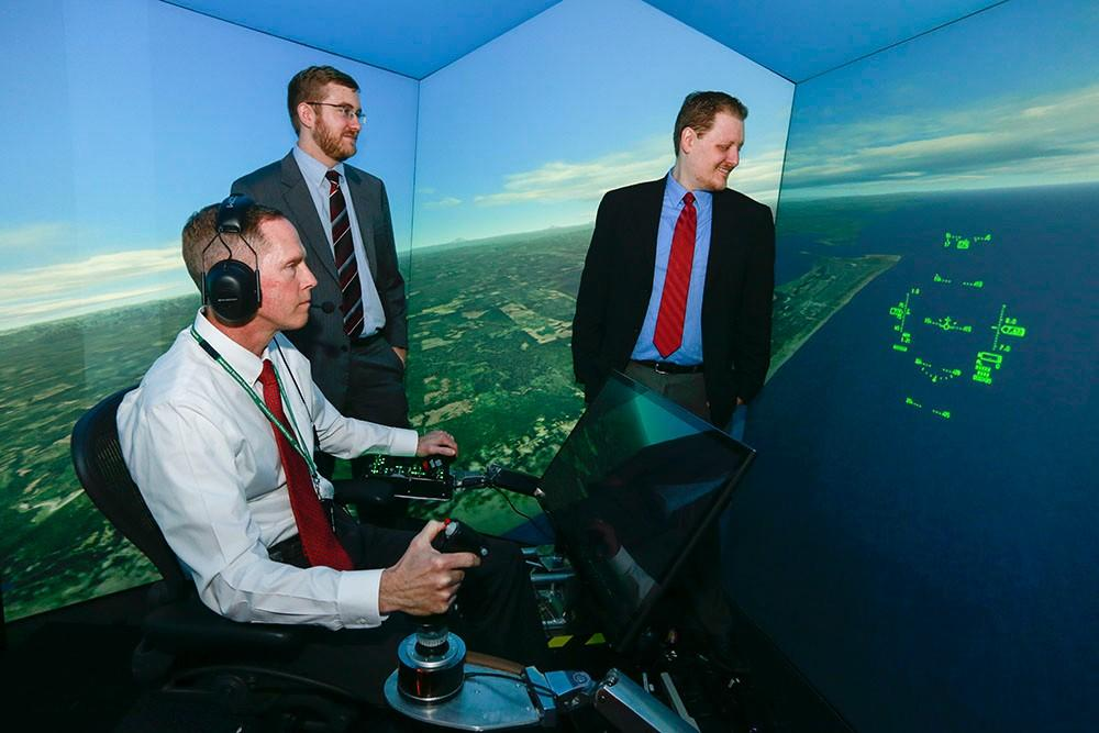 Standing at left is Psibernetix President and CEO Nick Ernest. David Carroll, also of Psibernetix, is standing at right. Seated at the simulator controls is retired U.S. Air Force Colonel Gene Lee