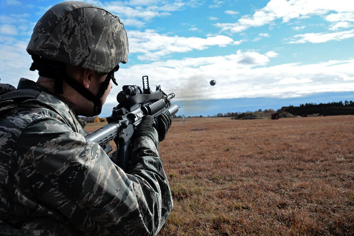 A grenade launcher dispenses a conventional 40-mm round