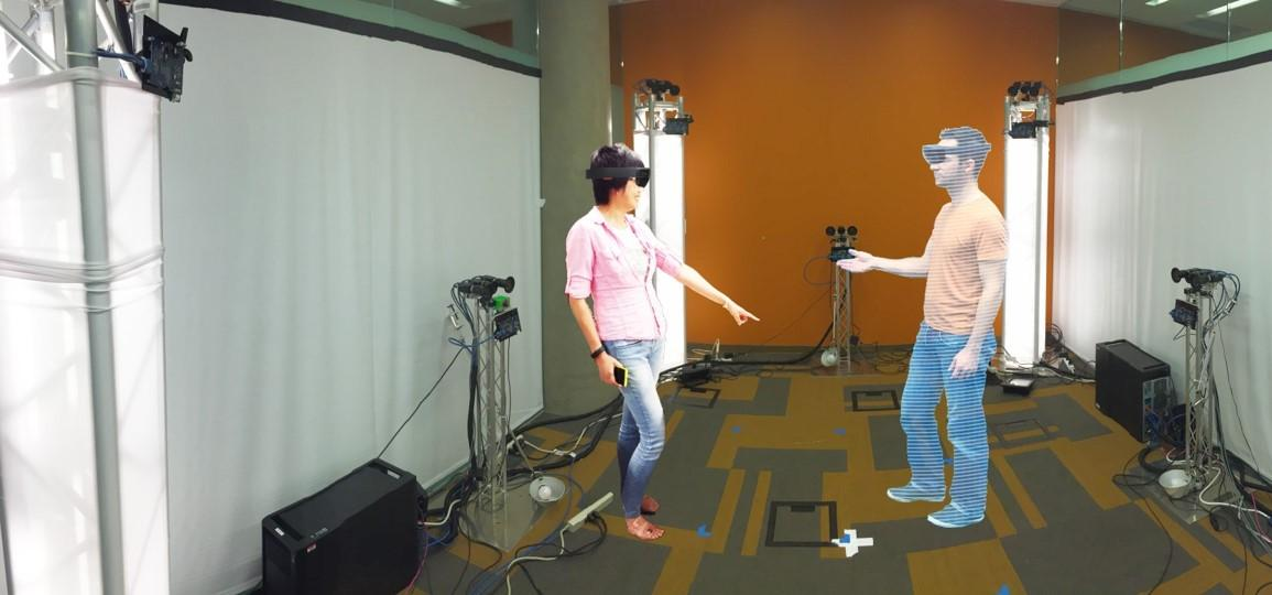 A person on the left wearing a HoloLens interacts with a 3D rendering of another person via holoportation on the right