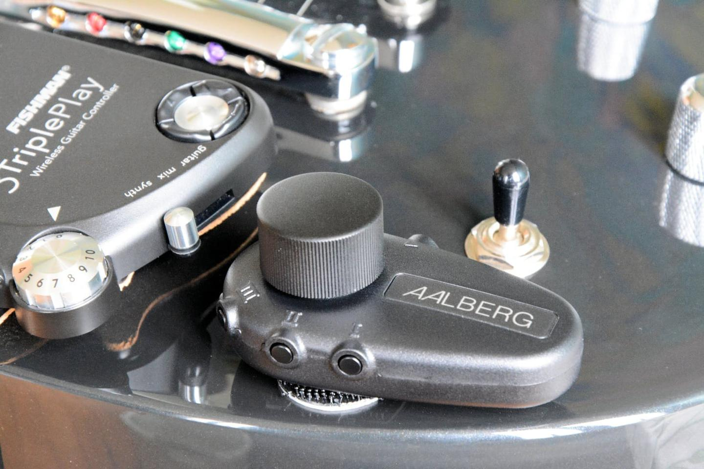 The Aalberg Audio Aero Bluetooth controller attaches to a guitar's body with adhesive-backed Velcro