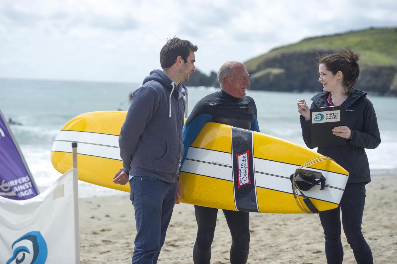 Dr. Anne Leonard interviews surfers on a beach in Cornwall, UK