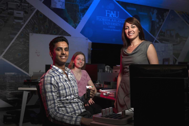 PhD studentMurtadha D. Hssayeni (left, holding one of the sensors), computer science majorLillian Boettcher, and Asst. Prof.Behnaz Ghoraani