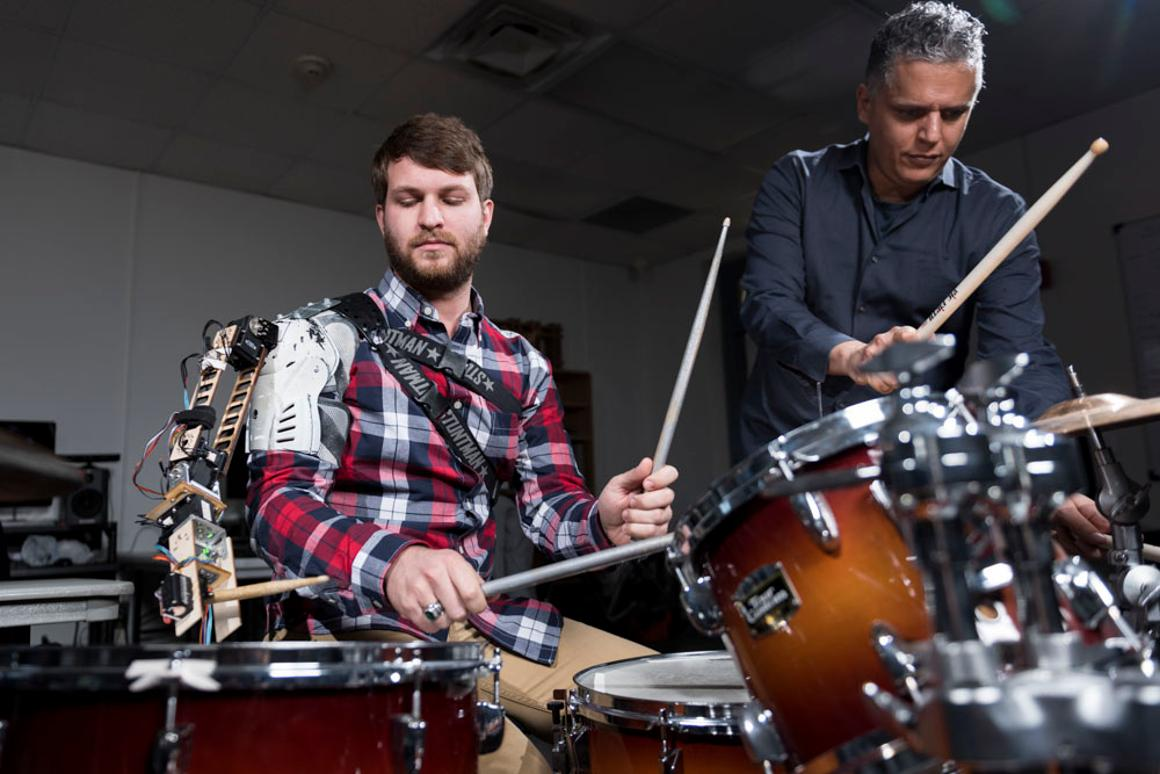 "Tyler White (left) with the ""third arm"" robotic drumming arm accompanied by Professor Gil Weinberg (right)"