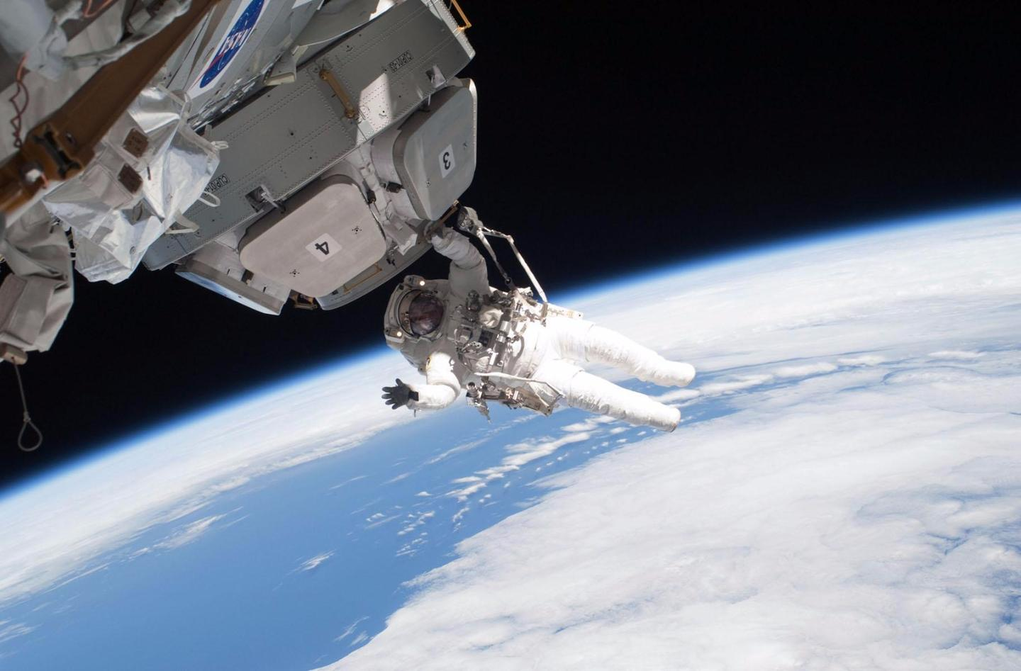Astronaut tethered to the cupola module of the International Space Station