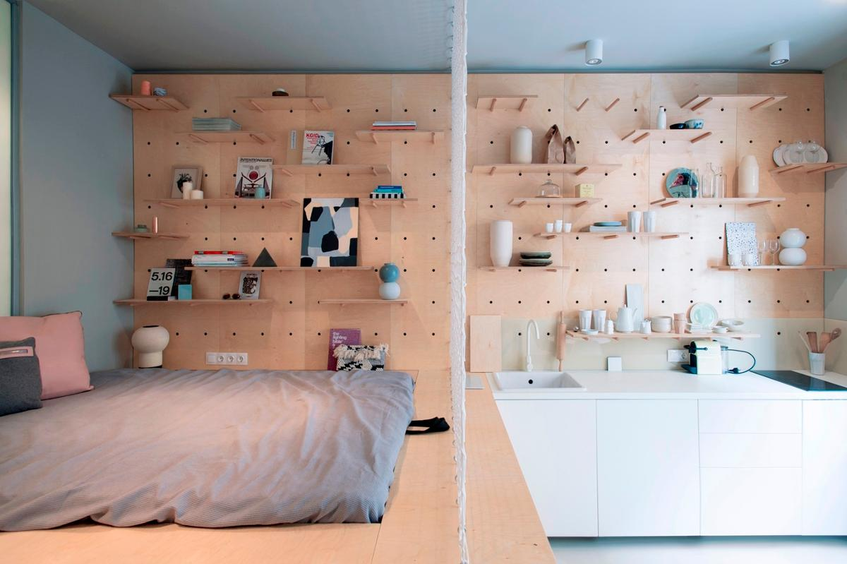 A net between the bed and the kitchen acts as a visual partition and could be used as a place to hang photos