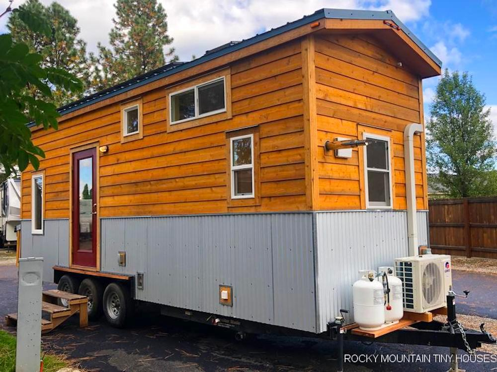 The Bradford 26' Tiny House's exterior is finished in cedar siding, with corrugated metal accenting