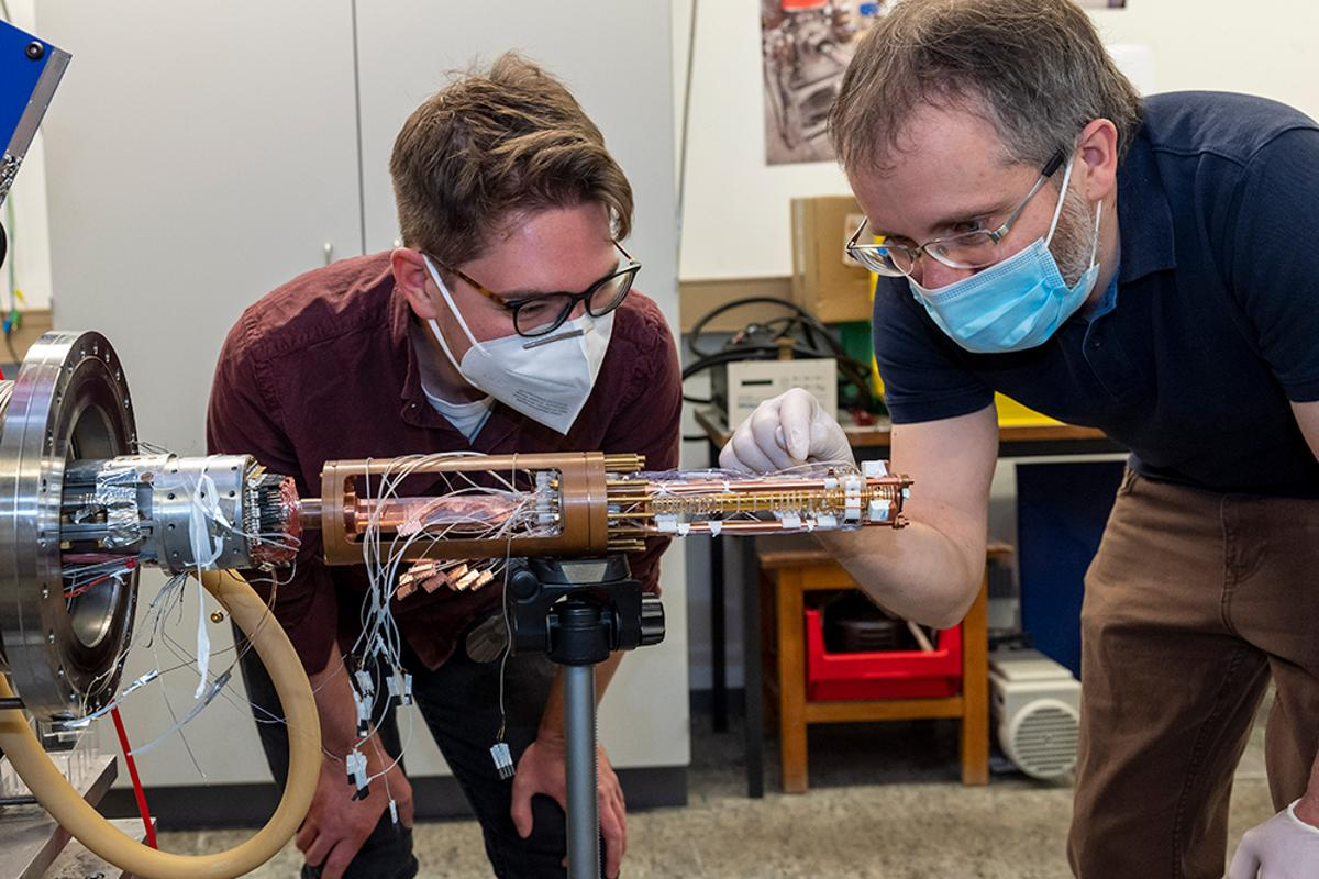 Researchers Matthew Bohman (left) and Christian Smorra (right) with the new two-trap cooling system