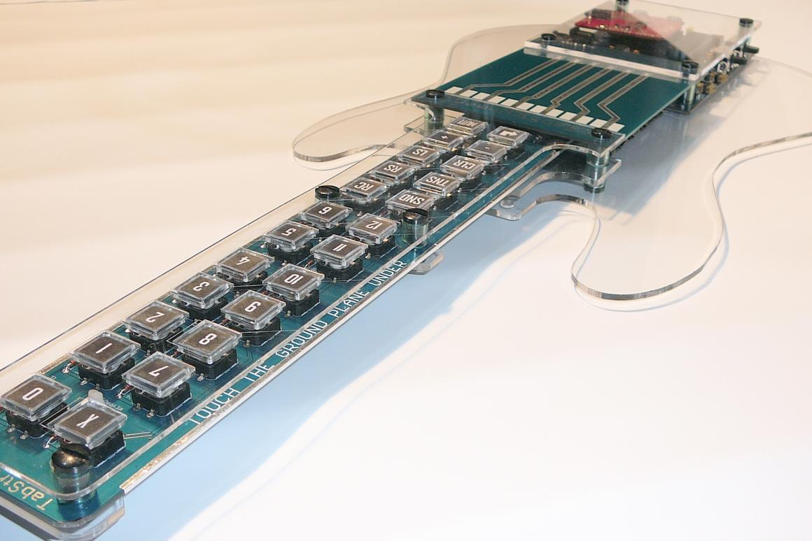 The guitar-shaped Tabstrummer programmable MIDI controller allows users to create and register guitar chords to buttons on the neck and strum songs via PCB strings