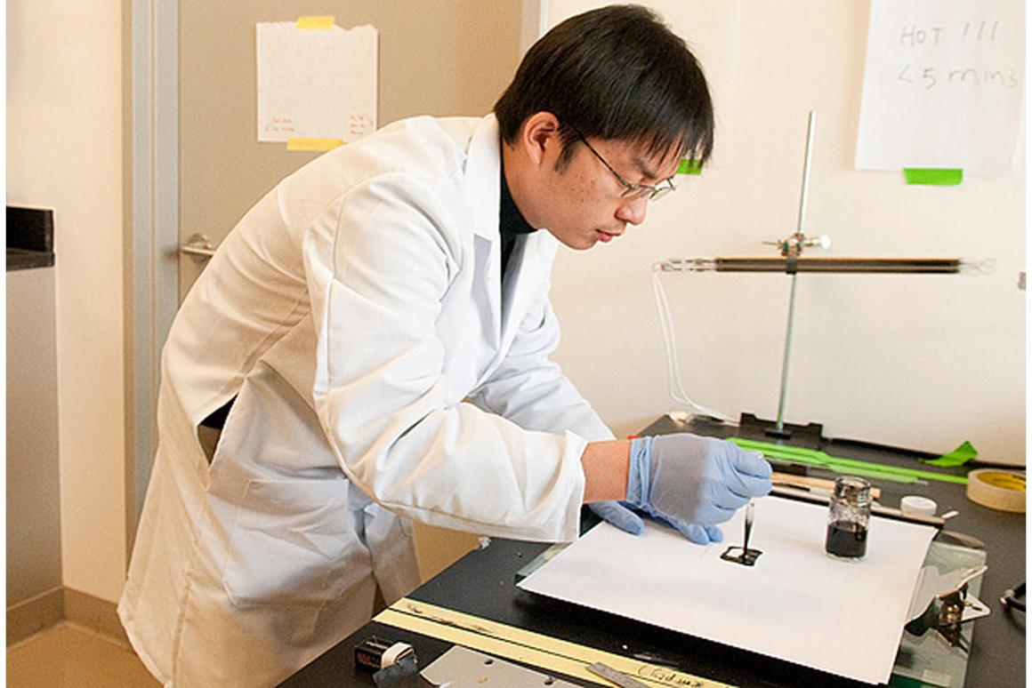 Researcher Bing Hu paints a small square of ordinary paper with an ink that will deposit nanotubes on the surface that can then be charged with energy to create a battery