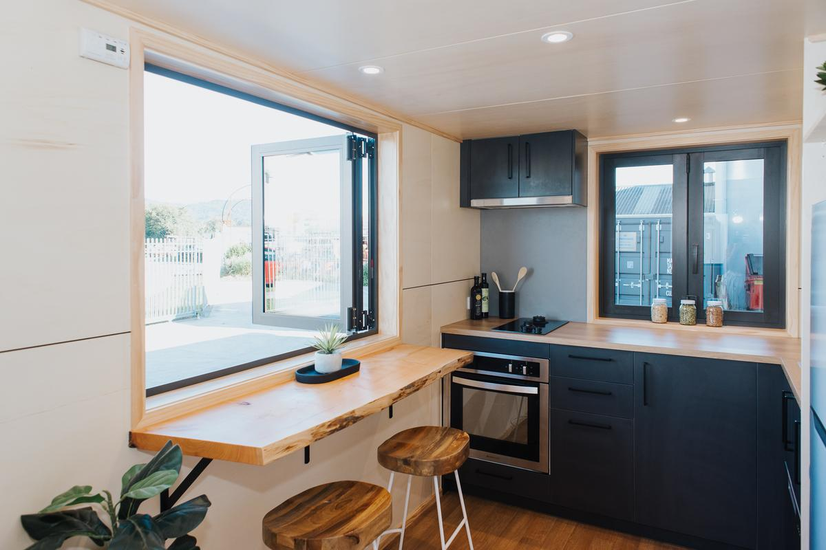 Scotty The Tiny House's kitchen includes a seating area for two with bifold windows. The kitchen benches are slightly higher than you might find in other builds, to suit the owners (who happen to be quite tall)