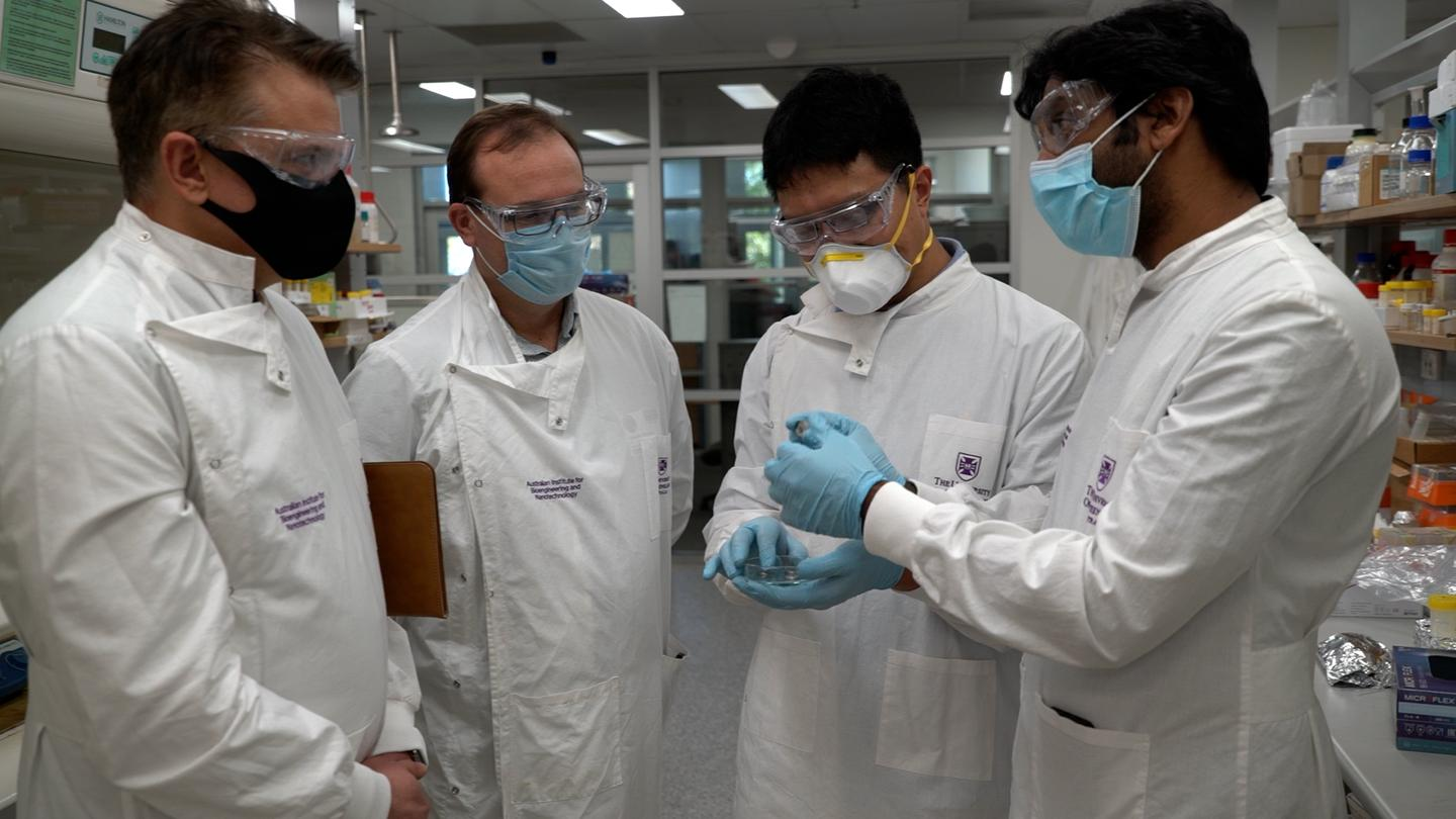 From left to right: Mr Craig Nicol (GMG), Mr Timothy Scheiwe (GMG), Dr Ashok Nanjundan (GMG) and Dr Xiaodan Huang (AIBN), standing around showing each other coin cells as if they've been asked to by a photographer
