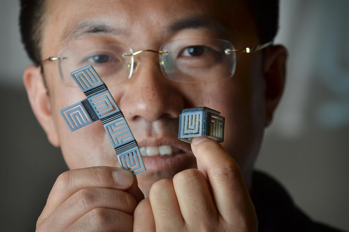 Prof. H. Jerry Qi with identical 4D-printed objects in their flat and folded states